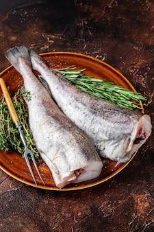Bacalhau ou bacalhau cru crus em prato rústico com ervas e garfo. vista do topo.