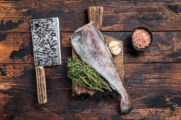 Bacalhau ou bacalhau fresco cru na placa de madeira com cutelo. mesa de madeira escura. vista do topo.