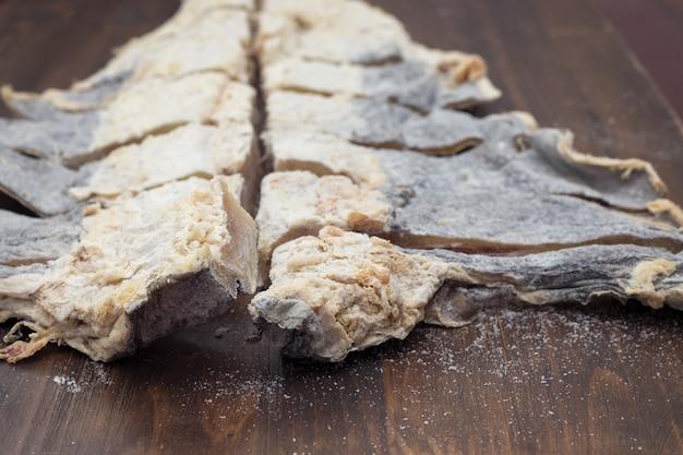 Bacalhau salgado seco na superfície de madeira marrom