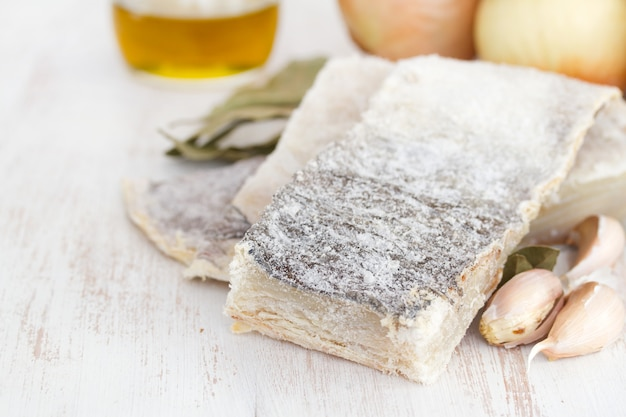 Bacalhau seco salgado com azeite, alho e cebola na superfície de madeira