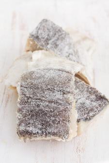 Bacalhau seco salgado na superfície de madeira branca