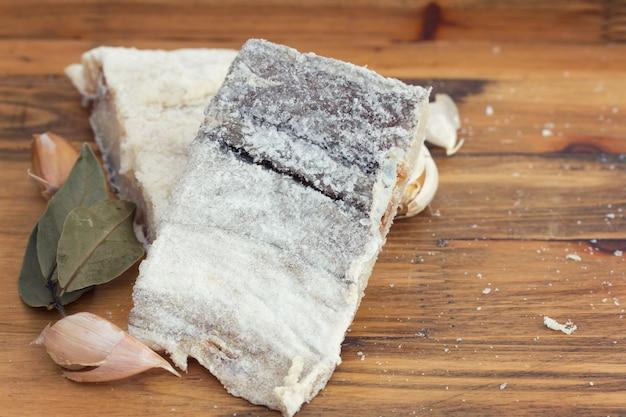Bacalhau seco salgado na superfície de madeira