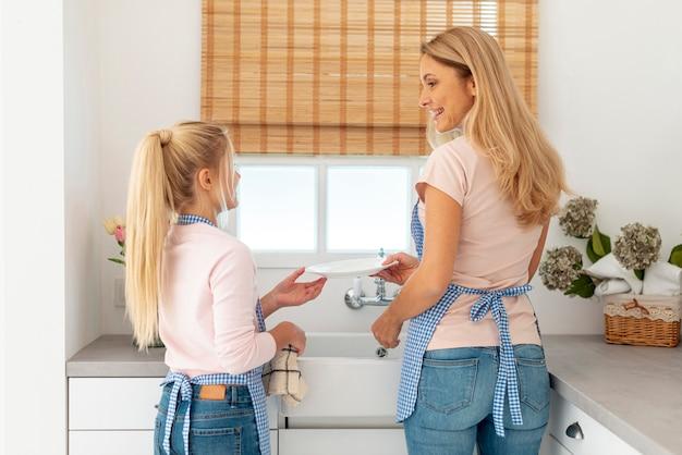 Bach vista mãe e filha limpando pratos