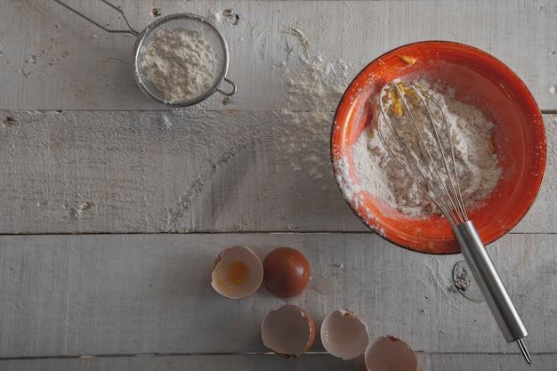 Bacia alaranjada com farinha, ovos e um batedor para fazer a massa em um fundo de madeira branco.