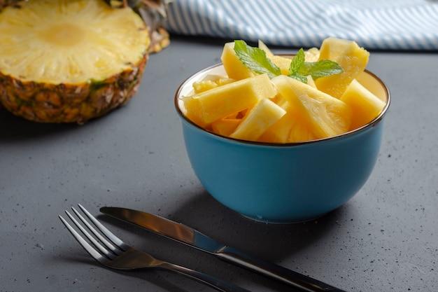 Bacia azul com abacaxi fresco e talheres