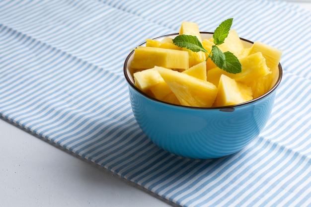 Bacia azul com abacaxi fresco na toalha de mesa listrada leve