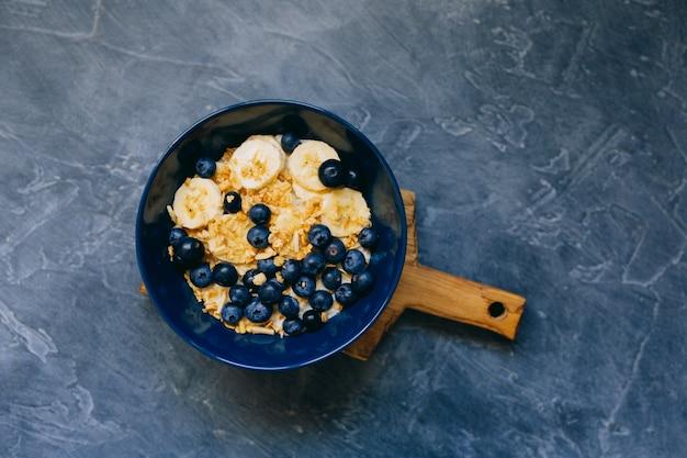Bacia azul escura de mingau de aveia com banana e mirtilo na vista superior de mesa vintage em estilo plano leigo. café da manhã quente e comida caseira. espaço livre. cozinha caseira.