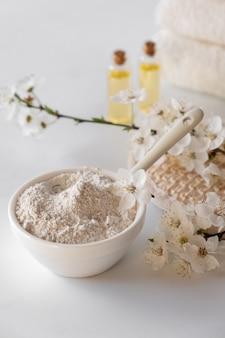 Bacia cerâmica com pó de argila branca na superfície branca. ingredientes para a máscara facial e corporal caseira ou esfoliação e raminho fresco de cerejeira. conceito de spa e cuidados com o corpo.