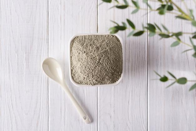 Bacia cerâmica com pó de argila verde e folhas frescas de eucalipto em fundo branco. conceito de cuidados com o rosto e corpo. vista do topo