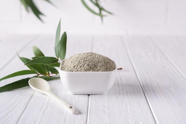 Bacia cerâmica com pó de argila verde e folhas frescas de eucalipto em fundo branco. conceito de cuidados com o rosto e corpo.