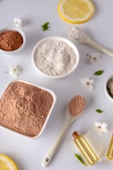 Bacia cerâmica com pó de argila vermelha, ingredientes para máscara facial e corporal caseira ou esfoliação e raminho fresco de cereja de florescência na superfície branca. conceito de spa e cuidados com o corpo.