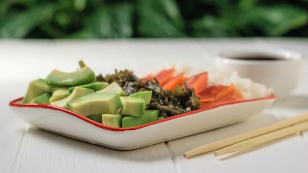 Bacia com arroz, abacate, salmão e alga marinha em uma mesa de madeira branca contra uma árvore verde.