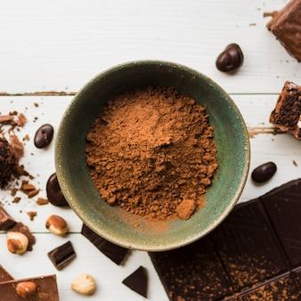 Bacia com cacau perto de doces de chocolate