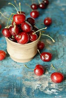Bacia com cerejas frescas sobre um fundo azul de madeira. cerejas maduras. conceito de comida saudável. cerejas em uma tigela de cerâmica.
