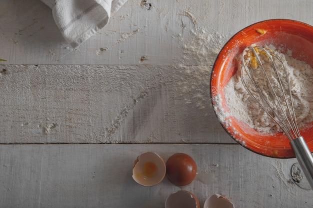 Bacia com farinha, ovos e um batedor para fazer a massa sobre um fundo branco de madeira.