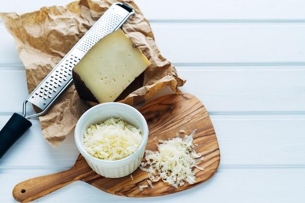 Bacia com queijo ralado em uma tábua. copie o espaço.