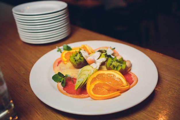 Bacia com salada de frutas frescas e bagas isoladas no branco.
