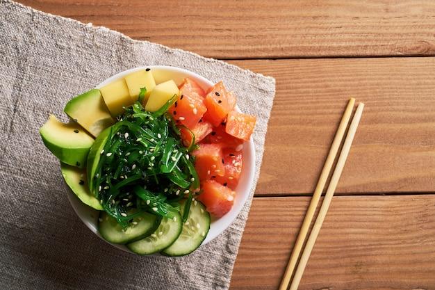Bacia com salmão, abacate, salada chuka, manga, polvilhada com pauzinhos e molho de soja
