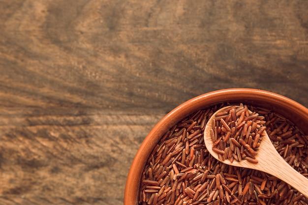 Bacia de arroz integral de jasmim marrom na mesa de madeira