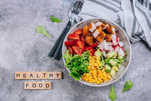 Bacia de biddha de almoço saudável. abacate, frango, tomate, rabanete, milho, folhas verdes salada de legumes.