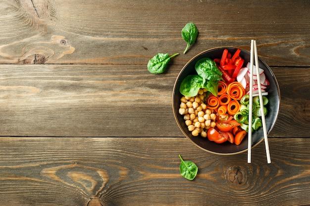Bacia de buda colorido com grão de bico, cenoura, tomate, pepino, rabanete e pimentão na mesa de madeira. salada vegetariana. vista do topo. copie o espaço.