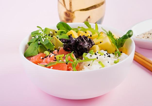 Bacia de buda com arroz, manga, abacate e salmão. comida saudável.