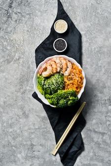 Bacia de buddha com camarões, abacate, cenoura, bróculos e arroz. comida equilibrada.