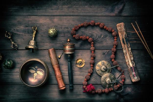 Bacia de canto de cobre, contas de oração, tambor de oração e outros objetos religiosos tibetanos para meditação