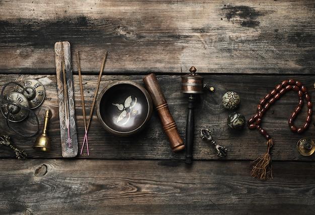 Bacia de canto de cobre, contas de oração, tambor de oração e outros objetos religiosos tibetanos