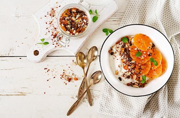 Bacia de granola caseiro com iogurte e tangerina na tabela de madeira branca. comida de fitness. vista do topo