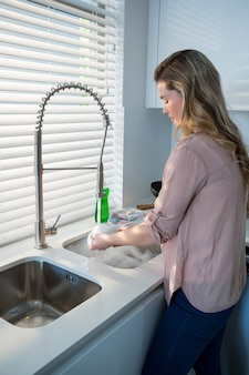 Bacia de lavagem da mulher sob a pia na cozinha