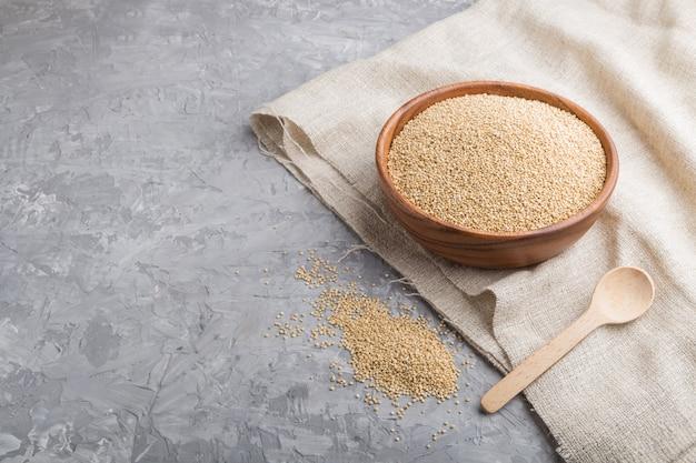 Bacia de madeira com as sementes de quinoa brancas cruas e colher de madeira em um fundo concreto cinzento. vista lateral, copie o espaço.