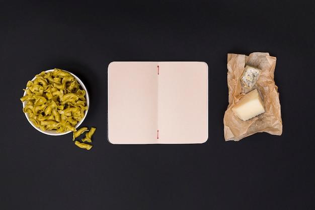 Bacia de massas alimentícias não cozidas; diário aberto em branco e queijo na parte superior da cozinha