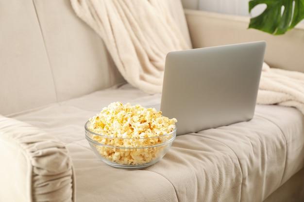 Bacia de pipoca e laptop no sofá. assistindo filmes em casa