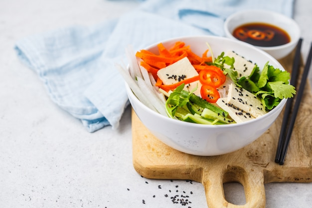 Bacia de salada do cha do bolo do vegetariano. macarrão de arroz vietnamita com salada de legumes tofu e chili em tigela branca