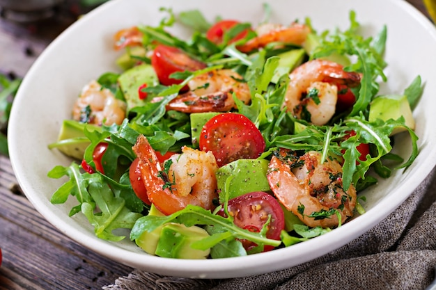Bacia de salada fresca com camarão, tomate, abacate e rúcula no fim de madeira do fundo acima.