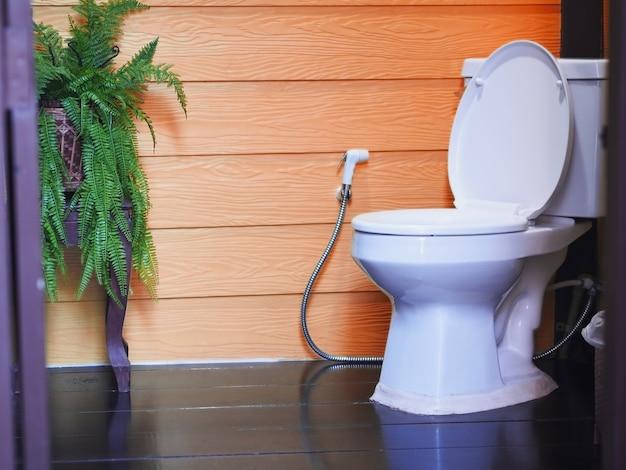 Bacia de toalete branca contra as telhas de madeira alaranjadas da parede no banheiro.