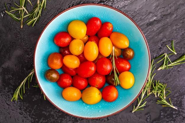 Bacia de tomates de cereja coloridos (vermelho, granada e amarelo), frescos e crus. com gotas de água e alecrim.