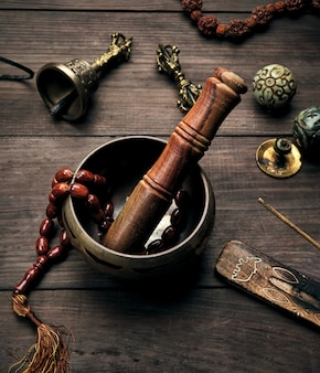 Bacia do canto de cobre e uma vara de madeira na mesa marrom