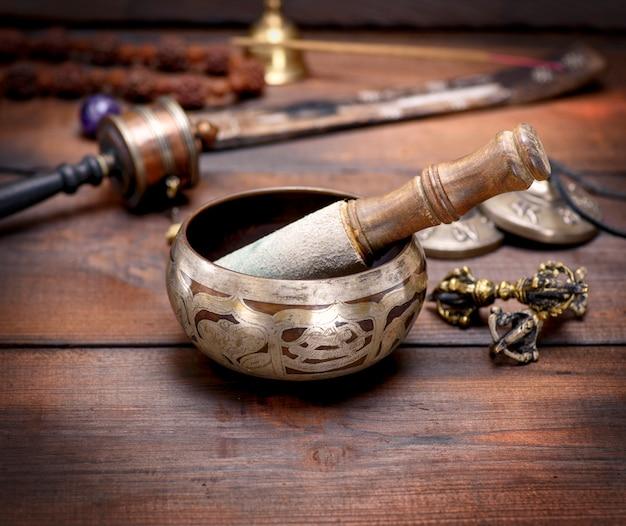 Bacia do canto de cobre e uma vara de madeira