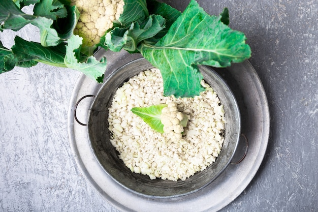 Bacia do metal de arroz da couve-flor no cinza. vista do topo. a sobrecarga. copyspace. desfiado
