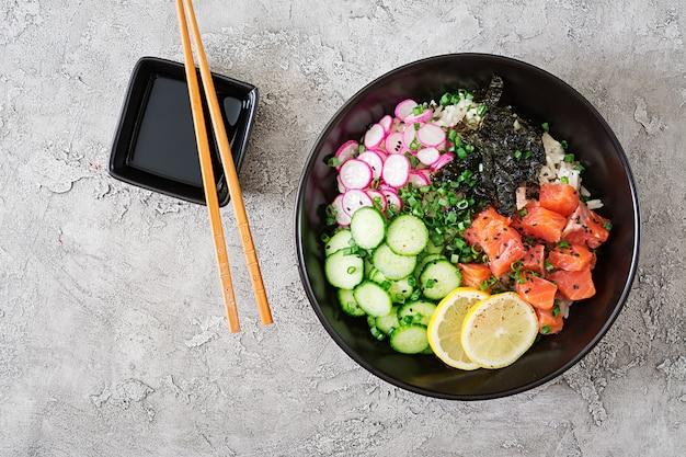 Bacia do poke do salmão havaiano com arroz, rabanete, pepino, tomate, sementes de gergelim e algas