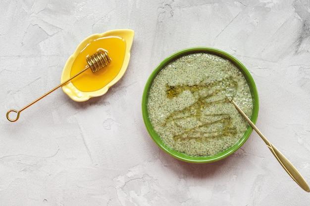 Bacia do pudim da semente do chia do chá verde de matcha com mel. conceito de superalimento e vegan.