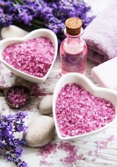 Bacia em forma de coração com sal marinho, óleos, sabão e flores frescas de alfazema em um fundo de madeira