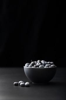 Bacia escura com cranberries em um fundo escuro