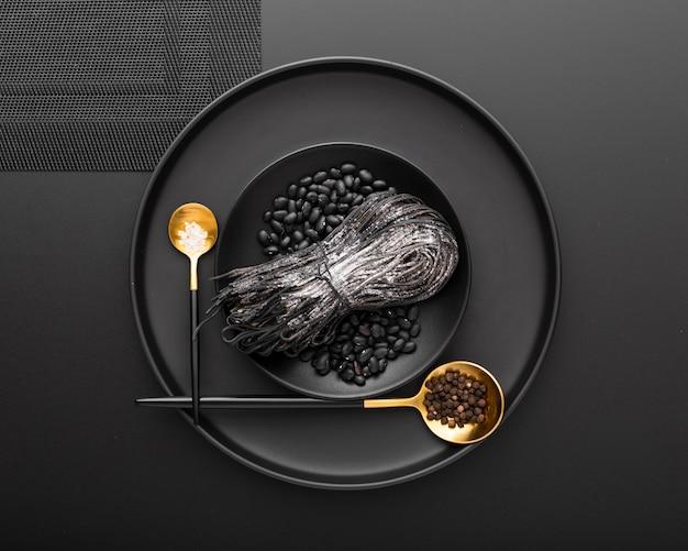 Bacia escura com macarrão e feijão com colheres em um fundo escuro