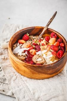 Bacia na moda do vegetariano de papa de aveia da farinha de aveia com bagas, as bolas cruas do vegetariano e a manteiga de amendoim.