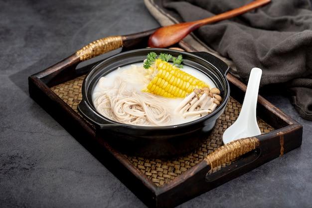 Bacia preta com macarrão e cogumelos com milho em uma mesa de madeira