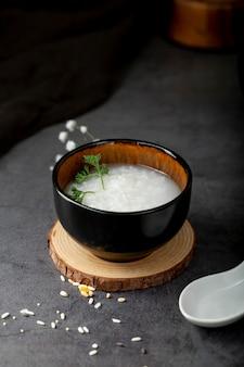 Bacia preta com sopa de arroz em um suporte de madeira