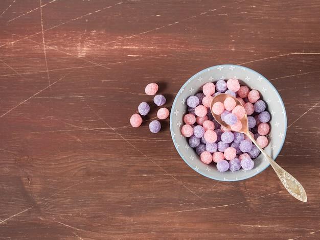 Bacia roxa e cor-de-rosa dos doces em de madeira